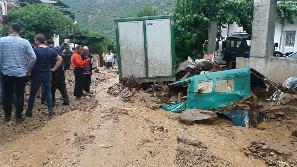 """AYDIN'ın Nazilli ilçesinde sağanak yağmurun ardından su baskını meydana geldi. Yüksek kesimlerden gelen sel suları nedeniyle dere taştı, evler ve tarlalar su altında kaldı.Nazilli'ye 18 kilometre mesafede, dağ yamacında yer alan kırsal Bağcıllı Mahallesi, sağanak yağmur nedeniyle yüksek kesimlerden akan yağmur sularının etkisi altında kaldı. Yaklaşık 1 saat süren sağanağın ardından yüksek kesimlerden akan sular, Bağcıllı mahallesinden geçen derenin taşmasına yol açtı. Çamur halinde akan taşkın nedeniyle sokaklardaki parke taşları söküldü, önüne kattığı motosiklet, traktör kasası ve arazi araçlarını sürükledi. Ekili alanlar su altında kalırken, ev ve işlerlerinin zemin katlarını da su baskı.    Sağanak sırasında evlerinden çıkamayan vatandaşlar, yağmurun dinmesiyle, hayvanlarının, tarlalarının ve araçlarının yanına gitti. Baskının ardından Nazilli Belediyesi ekipleri ve iş makinaları temizlik çalışması başlattı.Bağcıllı Mahallesi Muhtarı Hasan Güler, ilk belirlemelere göre can kaybının yaşanmadığı belirtirken, """"Yaklaşık 1 saatlik yağışta, her şey alt üst oldu. Geçen yıl da benzer bir olay yaşadık. Şimdi ne zarar var onu tespit etmeye çalışıyoruz"""" dedi.Mahalle sakinlerinden Arzu Ay ise geçen yıl da su taşkınının yaşandığını belirterek, """"Her yağışta sel baskını yaşıyoruz. Bu yıl da yaşandı, can kaybı olmadan bu baskınlara karşı bir önlem alınsın"""" diye konuştu."""